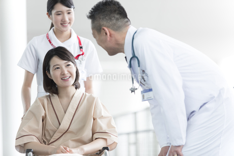 車椅子の患者に添う男性医師と女性看護師の写真素材 [FYI02973943]