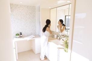 鏡の前で肌を見る女性の写真素材 [FYI02973951]