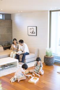 リビングで本を見る夫婦と床で遊ぶ姉妹の写真素材 [FYI02973953]