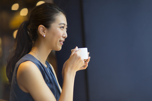 カフェでカップを持ってくつろぐ女性の横顔の写真素材 [FYI02973956]