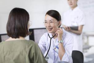 患者に聴診器をあてる女性医師の写真素材 [FYI02973957]