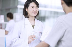 受付で薬の説明をする女性薬剤師の写真素材 [FYI02973958]