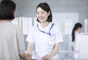 受付で対応を行う女性看護師の写真素材 [FYI02973962]