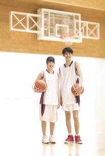 バスケットボールを持ち笑顔の男子学生と女子学生の写真素材 [FYI02973968]