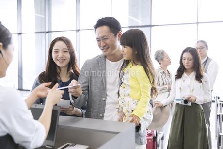 空港カウンターで手続きをする家族の写真素材 [FYI02973970]