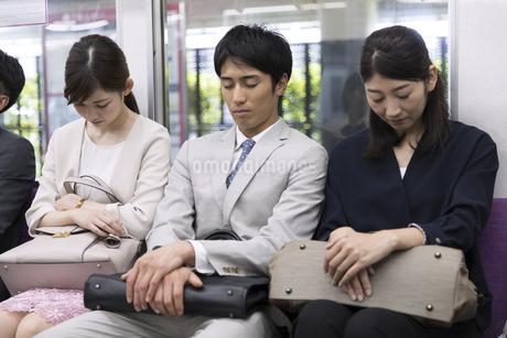 電車で眠るビジネス男性の写真素材 [FYI02973972]