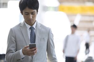 駅でスマホを見るビジネス男性の写真素材 [FYI02973988]
