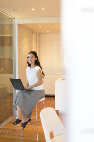 パソコンを開き遠くを見る女性の写真素材 [FYI02973990]