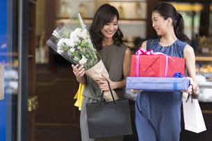 花束やプレゼントボックスを持って店を出る女性2人の写真素材 [FYI02973993]
