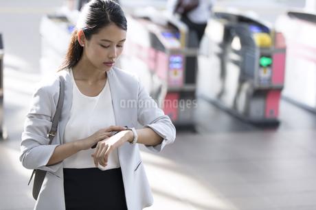 駅の改札付近で時計を見るビジネス女性の写真素材 [FYI02973996]