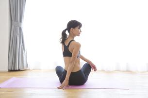 ヨガマットの上でストレッチをする女性の写真素材 [FYI02973997]