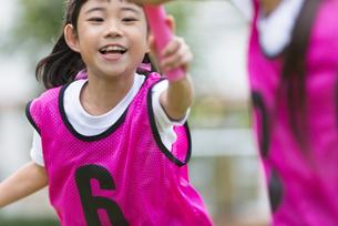 リレーのバトンを渡す女の子の写真素材 [FYI02973999]