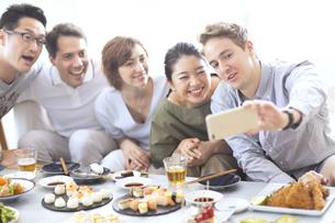 ホームパーティーで記念撮影をする外国人と日本人の写真素材 [FYI02974006]