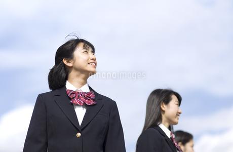 青空をバックに立つ女子高校生たちの写真素材 [FYI02974007]