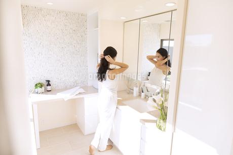 鏡の前で髪を整える女性の写真素材 [FYI02974008]