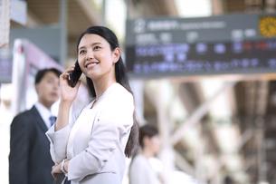 駅のホームで電話をするビジネス女性の写真素材 [FYI02974019]