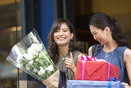 花束やプレゼントボックスを持って店を出る女性2人の写真素材 [FYI02974022]
