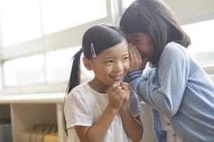 教室で内緒話をする女の子2人の写真素材 [FYI02974026]