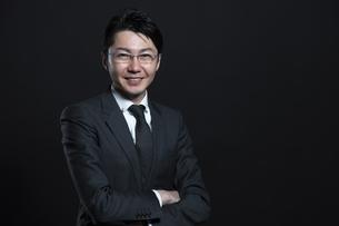 腕を組み微笑むビジネス男性の写真素材 [FYI02974027]