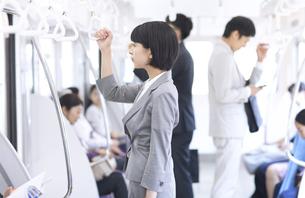 電車でつり革を持って立つビジネス女性の写真素材 [FYI02974028]