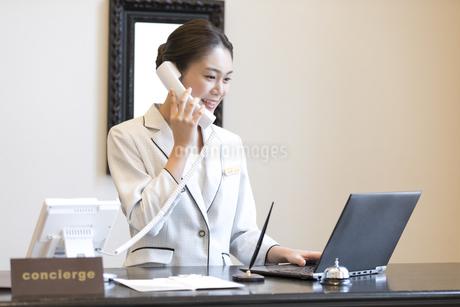電話対応をするコンシェルジュの女性の写真素材 [FYI02974032]