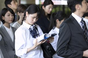駅のホームで勉強をする女子高校生の写真素材 [FYI02974040]