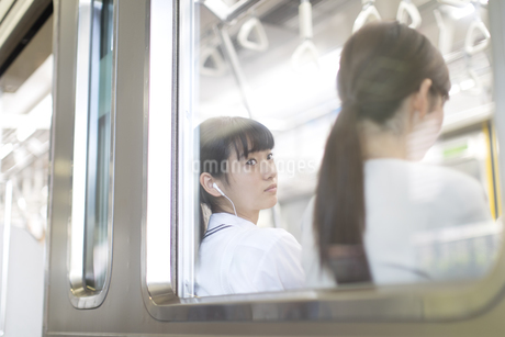 電車で音楽を聴きながら外の景色を見つめる女子高校生の写真素材 [FYI02974047]