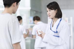 受付で薬の説明をする女性薬剤師の写真素材 [FYI02974054]