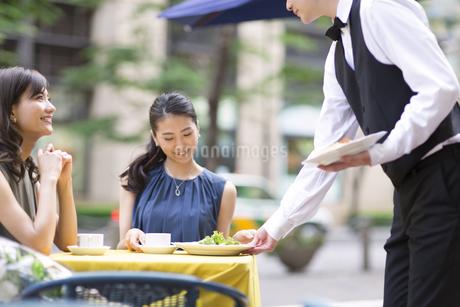 オープンカフェで食事をする女性2人の写真素材 [FYI02974056]