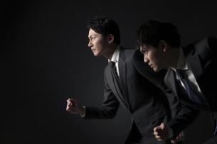駆け出すポーズをとるビジネス男性2人の写真素材 [FYI02974061]
