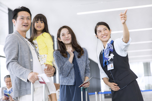 家族を案内する空港職員の写真素材 [FYI02974063]
