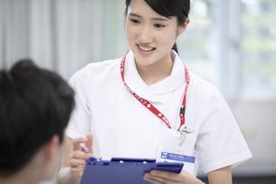 入院患者と会話をする女性看護師の写真素材 [FYI02974083]
