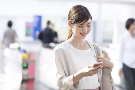 駅の改札付近でスマホを見るビジネス女性の写真素材 [FYI02974084]