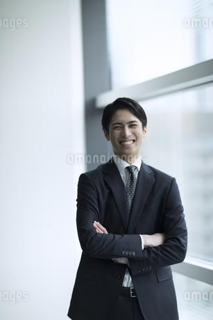 腕を組みカメラ目線で立つビジネス男性の写真素材 [FYI02974085]