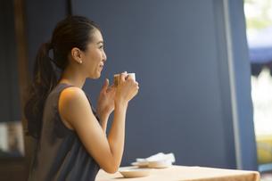 カフェでカップを持ってくつろぐ女性の横顔の写真素材 [FYI02974095]