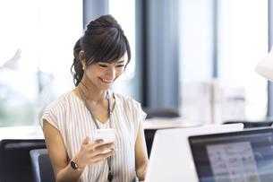 スマホを持ちPCを見るビジネス女性の写真素材 [FYI02974101]