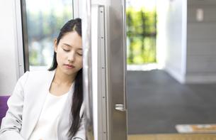 電車の座席に座り眠るビジネス女性の写真素材 [FYI02974103]