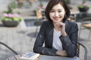 テラス席でカメラ目線のビジネス女性の写真素材 [FYI02974107]