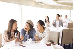 シャンパンを持ち会話をする3人の女性の写真素材 [FYI02974109]