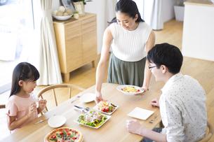 家族に食事を用意する母親の写真素材 [FYI02974116]