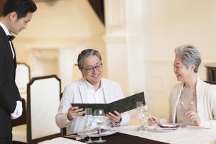 レストランでメニューを見るシニア夫婦の写真素材 [FYI02974117]