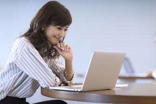 ペンを持ちノートパソコンを見るビジネス女性の写真素材 [FYI02974119]