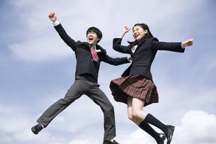 青空をバックにジャンプをする高校生たちの写真素材 [FYI02974121]