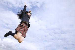 青空をバックにジャンプをする女子高校生の写真素材 [FYI02974122]