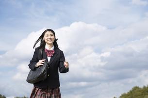 青空をバックに走る女子高校生の写真素材 [FYI02974123]
