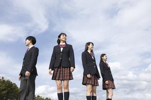 青空をバックに立つ高校生たちの写真素材 [FYI02974124]