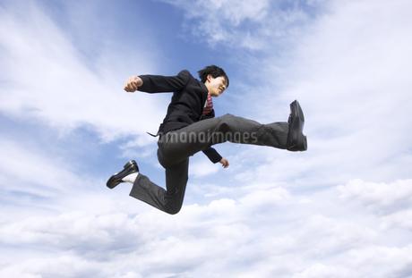 青空をバックにジャンプをする男子高校生の写真素材 [FYI02974128]
