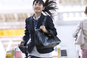 駅の改札を走って通過する女子高校生の写真素材 [FYI02974129]