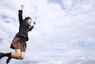 青空をバックにジャンプをする女子高校生の写真素材 [FYI02974132]