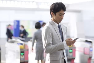 駅の改札付近でスマホを見るビジネス男性の写真素材 [FYI02974133]